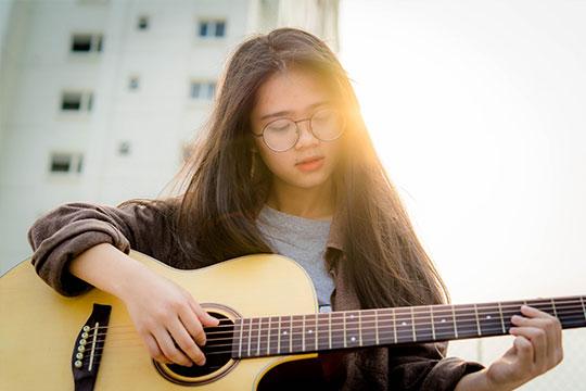 Seorang anak remaja bermain gitar